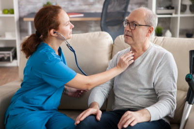 female nurse using stethoscope to listen the heart of old men in nursing home